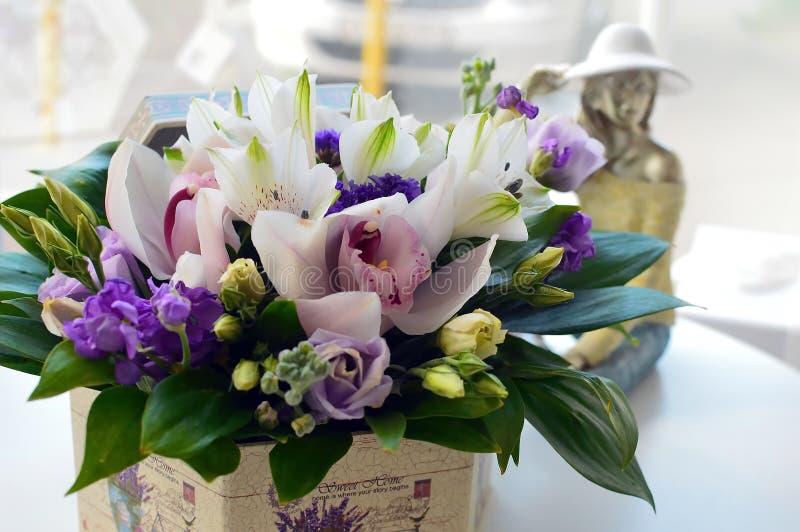 Försiktig bukett av orkidér i en stilfull hattask stock illustrationer