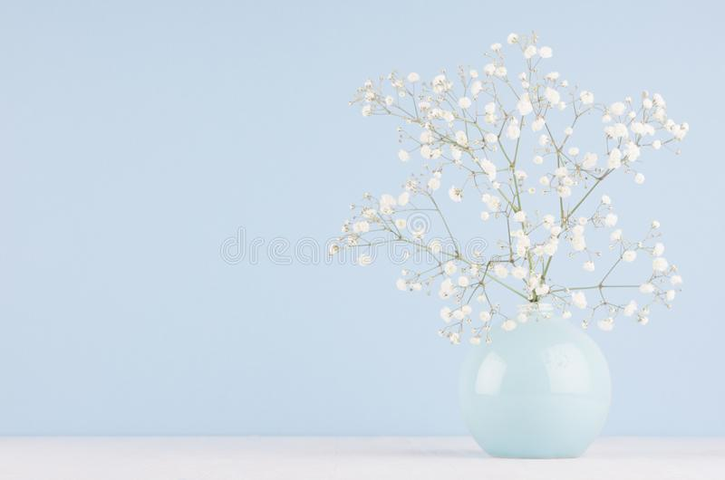 Försiktig elegant bukett av små blommor i keramisk cirkelbunke på mjuk pastellblåttbakgrund arkivbild