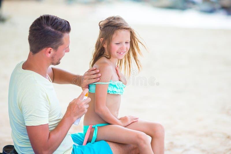 Försiktig fader som applicerar solkräm till ungenäsan Stående av lttleflickan i suncream arkivbilder