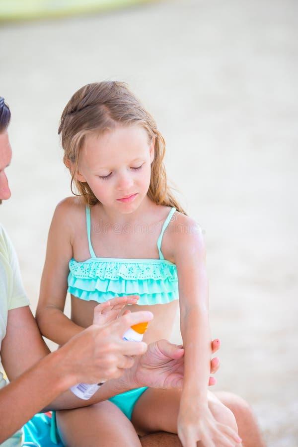 Försiktig fader som applicerar solkräm till ungenäsan Stående av lttleflickan i suncream royaltyfria foton