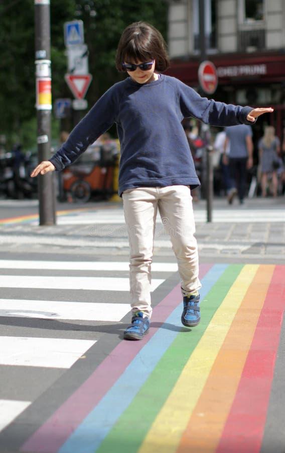 Försiktig flicka som balanserar armar som korsar den roliga gatan med serenitet arkivfoton