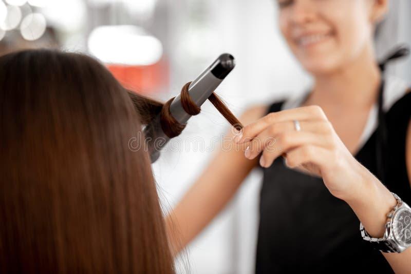 Försiktig frisör som rymmer krullande järn, medan arbeta med klienten arkivbild