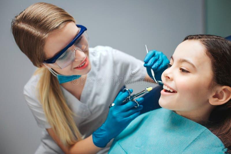Försiktig kvinnlig mun för flicka för tandläkarehållhjälpmedel nästan Barnshowframtänder Hon sitter i stillhet i tand- stol royaltyfri bild
