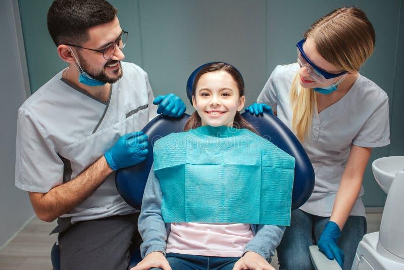 Försiktig positiv man och kvinnlig tandläkareblick på det ungepatienten och leendet Flickan sitter i tand- stol Hon ser rak och fotografering för bildbyråer