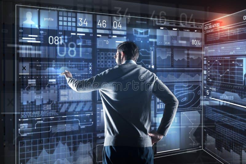 Försiktig programmerare som ser skärmen av hans apparat, medan studera information arkivbilder