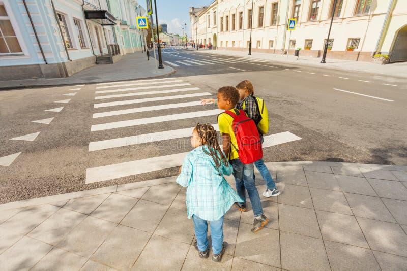 Försiktiga barn som korsar gatan royaltyfria bilder