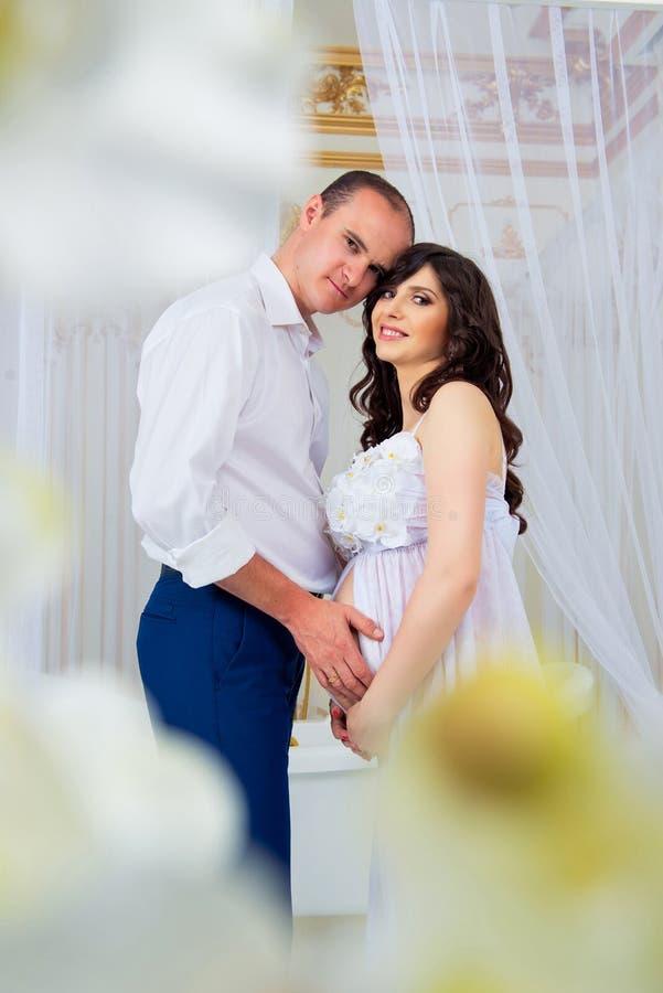 Försiktiga härliga gravida par nära tyllgardiner arkivfoto