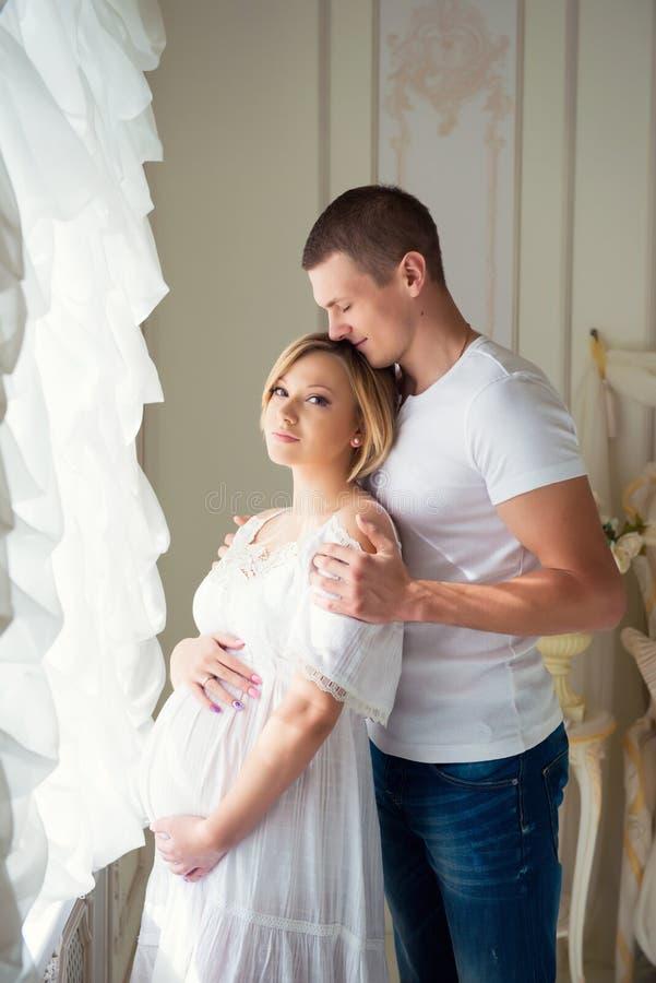 Försiktiga härliga gravida par nära tyllgardiner arkivbild