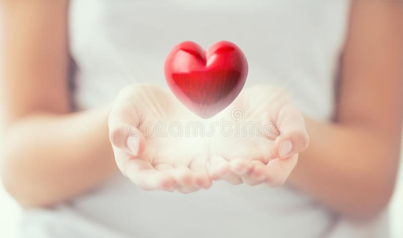 Försiktiga kvinnors händer och röda hjärta som glöder i hans händer Valentinmoderdag och välgörenhetbegrepp arkivfoto
