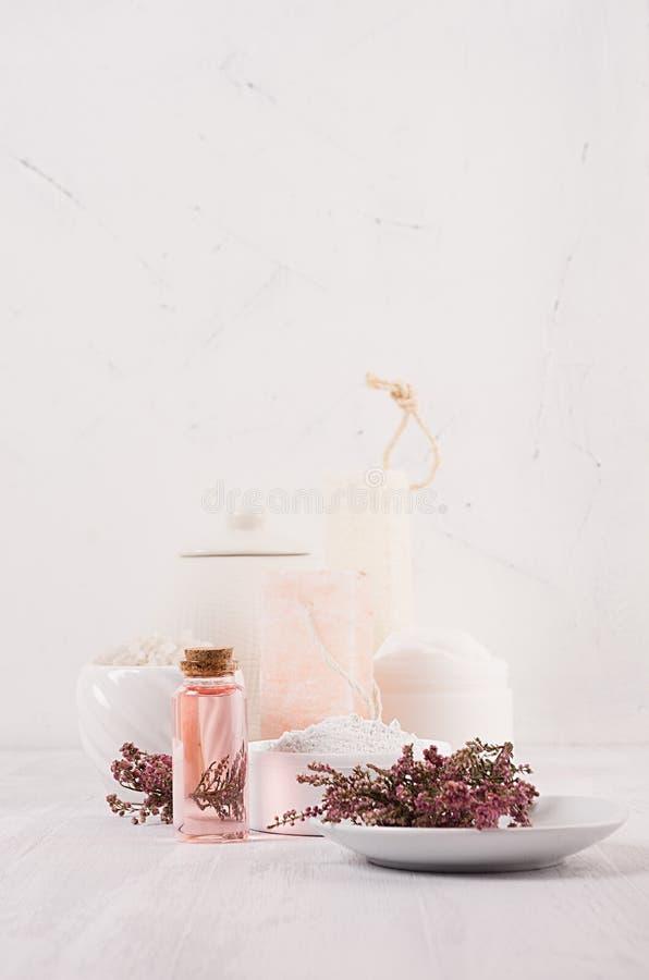 Försiktiga rosa skönhetsmedel oljer, små blommor och vit tvål, kräm, lera, handduk på den vita trähyllan, kopieringsutrymme, lodl royaltyfri bild