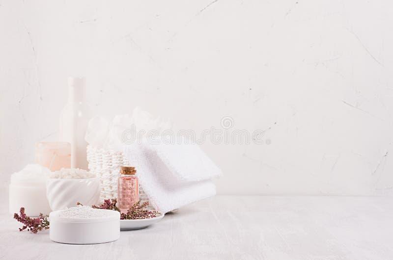 Försiktiga rosa skönhetsmedel oljer, små blommor och vit tvål, kräm, lera, handduk på den vita trähyllan, kopieringsutrymme, lodl arkivbild