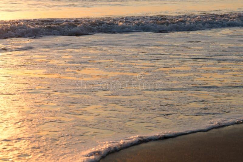 Försiktiga rullande vågor som bryter på fridsamt, tömmer stranden på soluppgång arkivfoton