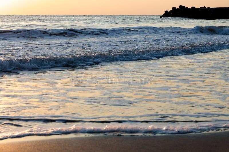 Försiktiga rullande vågor som bryter på fridsamt, tömmer stranden på soluppgång arkivbilder