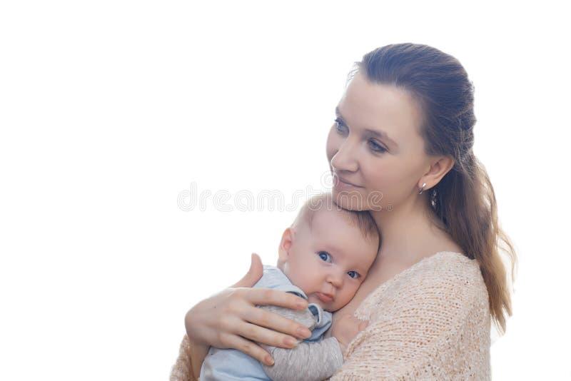 Försiktigt foto av modern och att behandla som ett barn Mamman med förälskelse och mjukhet kramar hennes son på en ljus bakgrund arkivfoton
