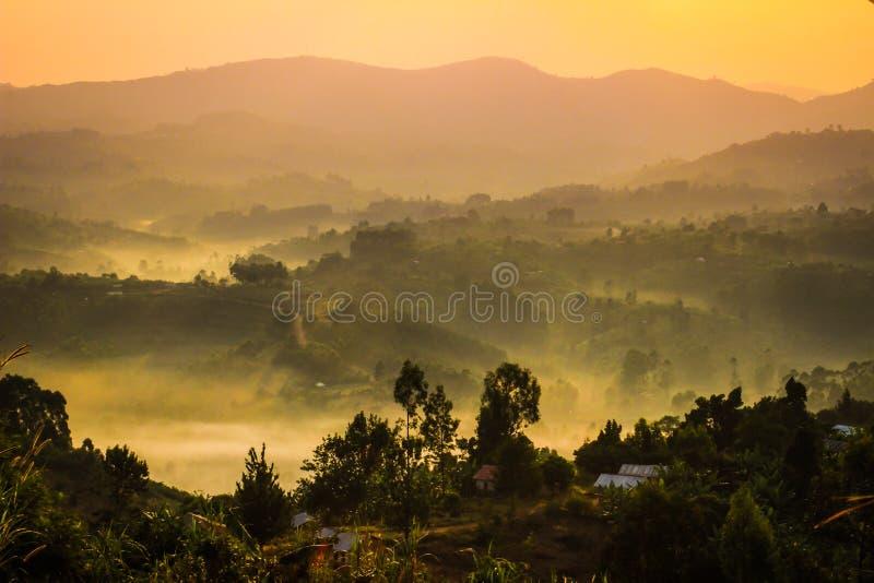 Försiktigt gult ljus och ljus mist över kullarna i landssida med traditionella hus och den tropiska naturen av Uganda arkivbild