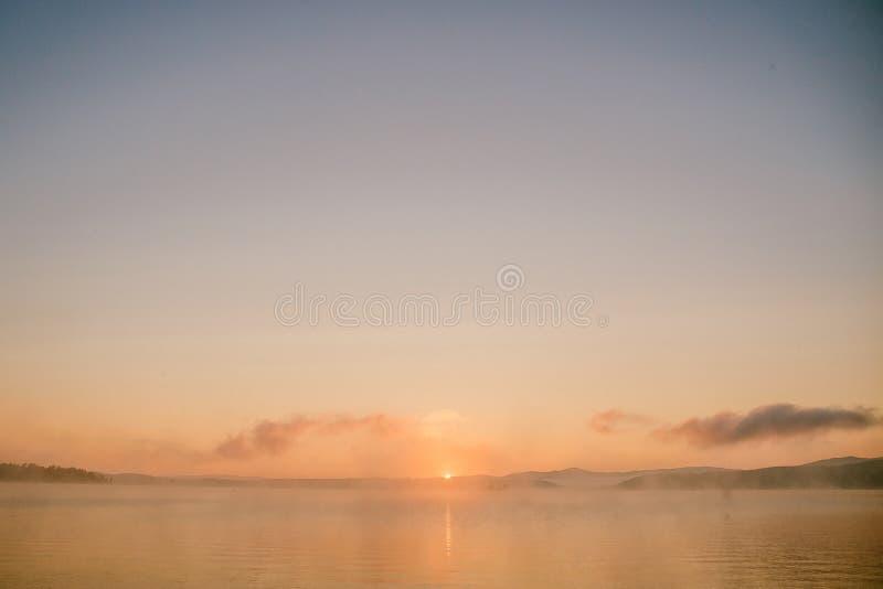 Försiktigt mjukt ljus - rosa färger gryr på den stora sjön, soluppgång, stillhet, dimma royaltyfria bilder
