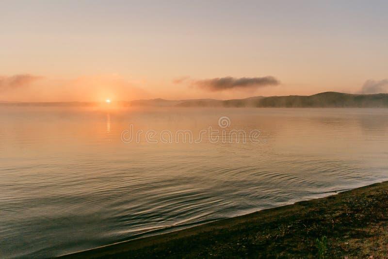 Försiktigt mjukt ljus - rosa färger gryr på den stora sjön, soluppgång, stillhet, dimma, horisontlinje royaltyfri fotografi
