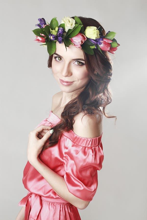 Försiktigt romantiskt utseende av flickan med en krans av rosor på hennes huvud och en rosa klänning Glad glad vårkvinna Sommarda arkivfoto
