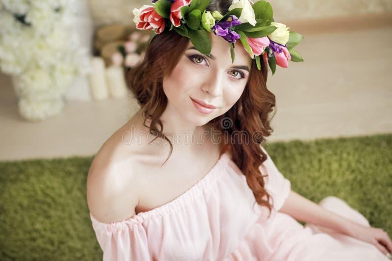 Försiktigt romantiskt utseende av flickan med en krans av rosor på hennes huvud och en rosa klänning Glad glad vårkvinna Sommarda royaltyfri fotografi