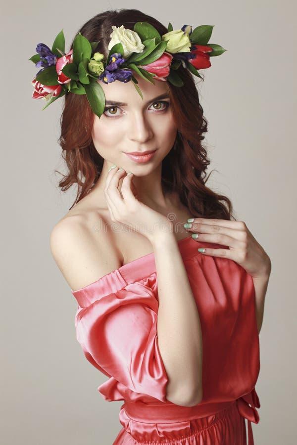Försiktigt romantiskt utseende av flickan med en krans av rosor på hennes huvud och en rosa klänning Glad glad vårkvinna Sommarda arkivbilder