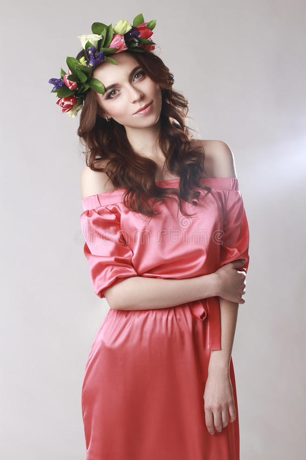 Försiktigt romantiskt utseende av flickan med en krans av rosor på hennes huvud och en rosa klänning Glad glad vårkvinna Sommarda arkivbild