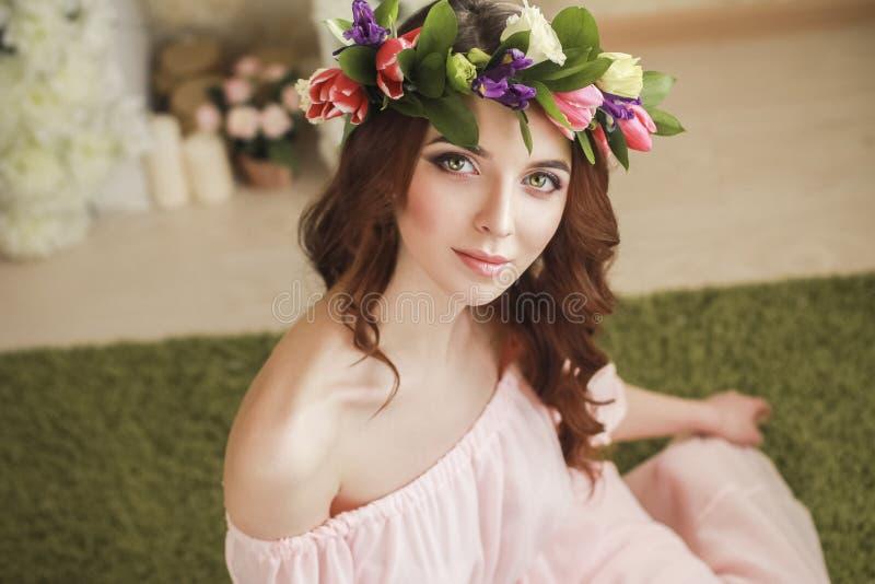 Försiktigt romantiskt utseende av flickan med en krans av rosor på hennes huvud och en rosa klänning Glad glad vårkvinna Sommarda royaltyfri foto