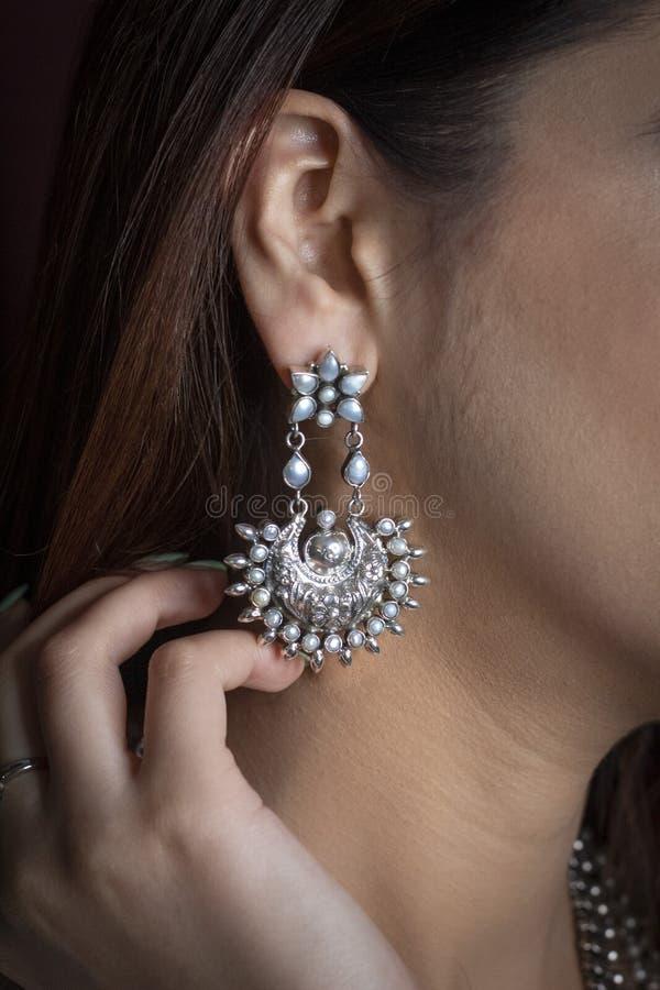 Försilvra örhänget på örat av en kvinna arkivbilder