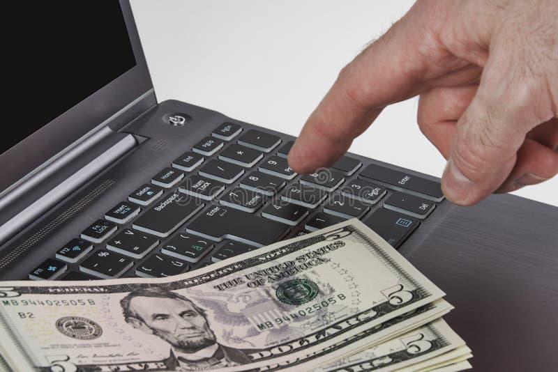 Försilvra bärbara datorn med dollarräkningar och händer som skriver på ett tangentbord royaltyfria bilder