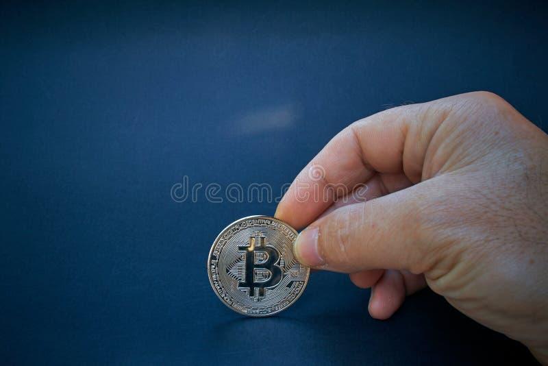 Försilvra Bitcoin är i den öppna handen Myntet skiner och reflekterar ljus Bakgrunden är mörk och abstrakt BTC-valutan är royaltyfria bilder