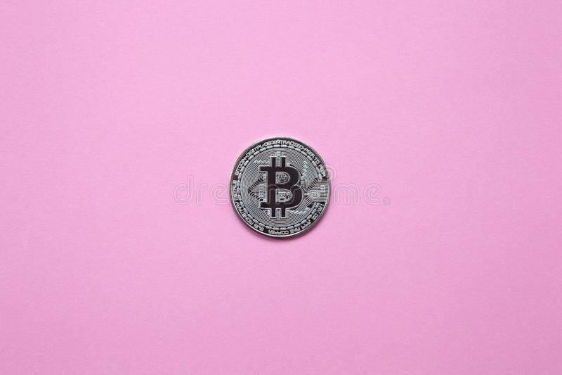 Försilvra bitcoin på en millennial rosa bakgrund Top beskådar minimalism En stor bakgrundsbild Lekmanna- lägenhet royaltyfri bild