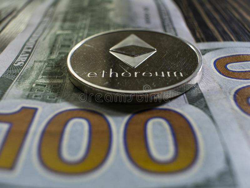 F?rsilvra Ethereum p? US dollar Digital valutan?rbild p? en tr?bakgrund Verkliga mynt av bitcoin p? sedlar av hundra royaltyfri fotografi
