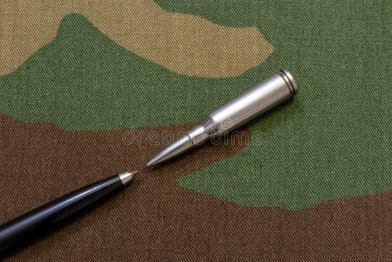 Försilvra gevärkulor mot pennan - ett tryckfrihetbegrepp royaltyfri bild