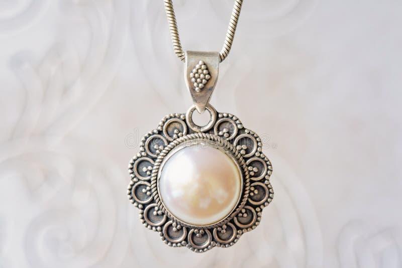Försilvra hängen med den vita stora pärlan royaltyfri foto
