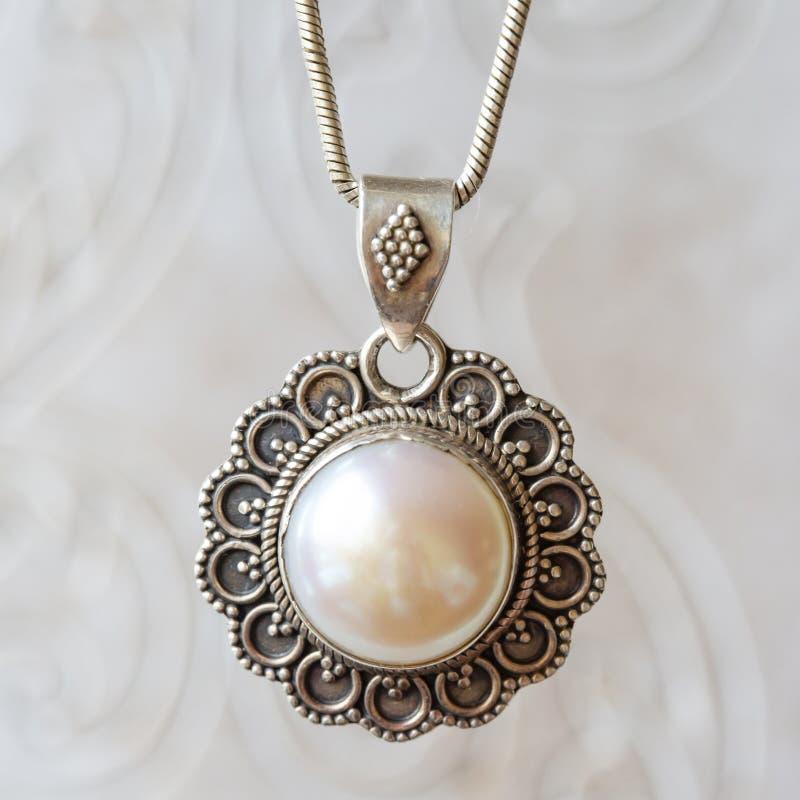 Försilvra hängen med den vita stora pärlan fotografering för bildbyråer