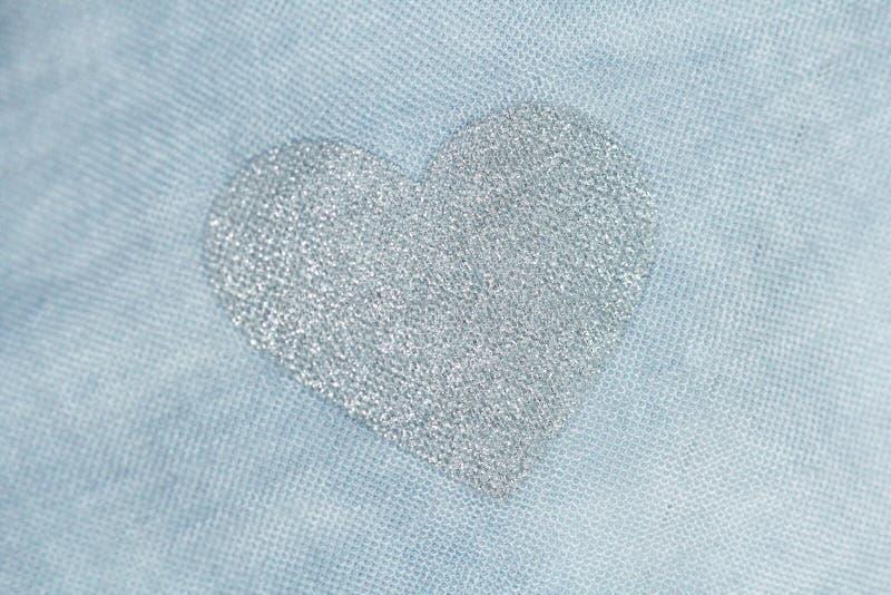 Försilvra hjärta på en blå bakgrund av bomullstyg Romantisk pas royaltyfri fotografi