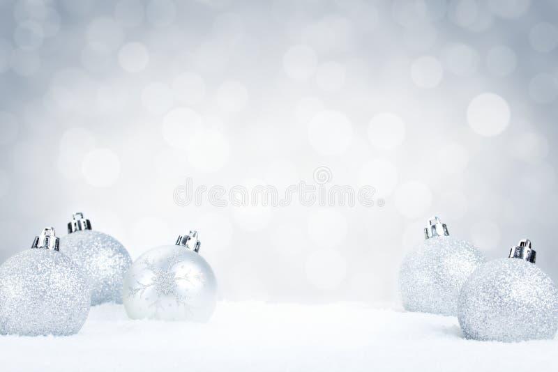 Försilvra julstruntsaker på snö med en silverbakgrund arkivfoto