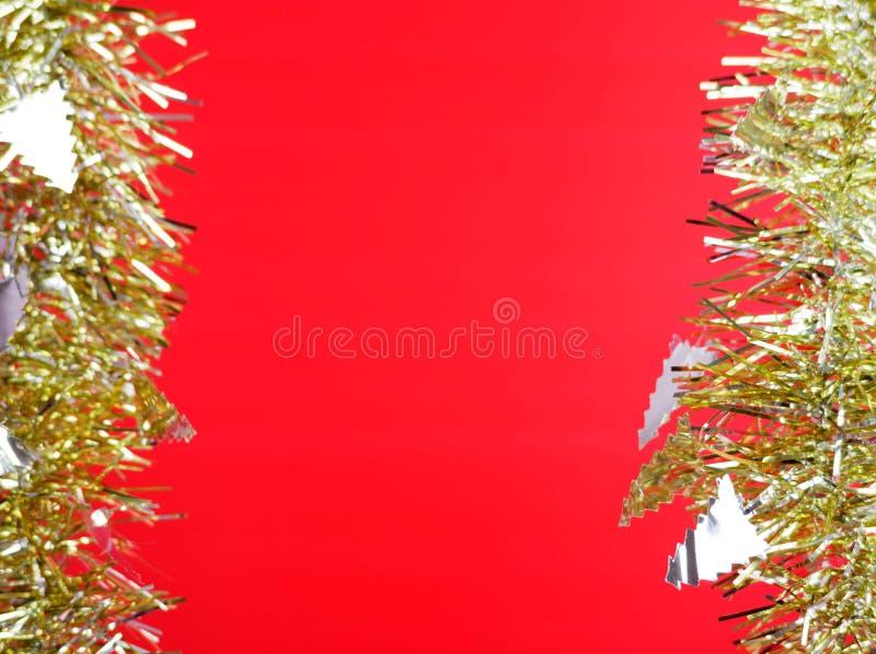 Försilvra julträdet och det guld- bandet på röd bakgrund arkivfoto
