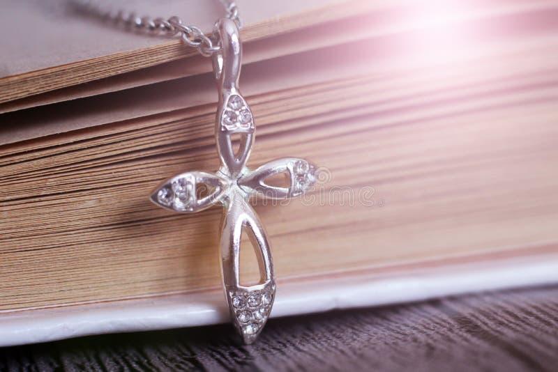 Försilvra korset på boken, smycken fotografering för bildbyråer