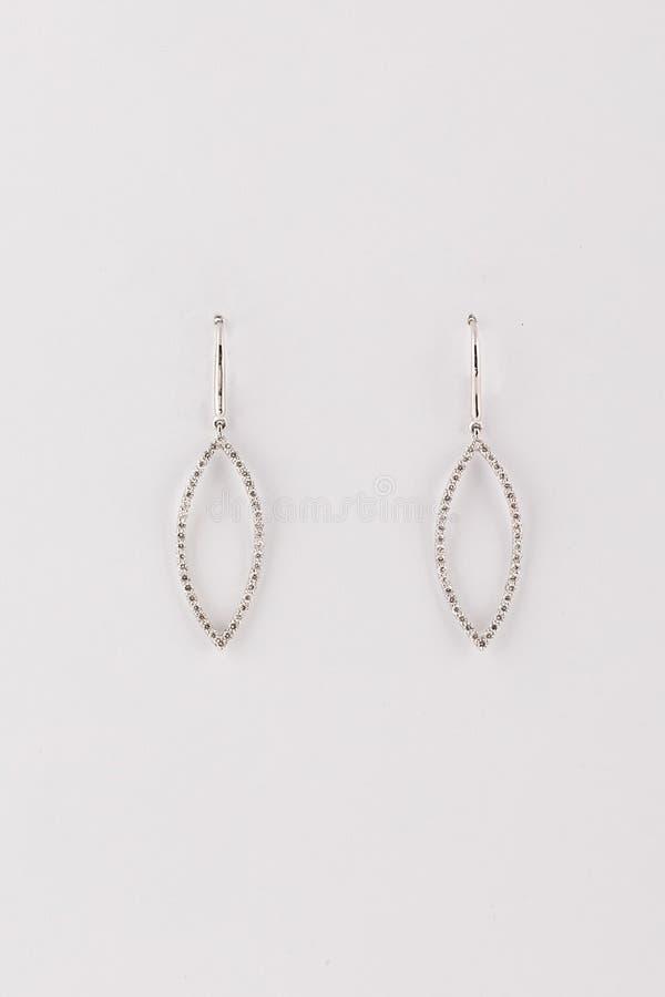 Försilvra kvinnors örhängen i formen av en ellips med diamanter som isoleras på en vit bakgrund arkivfoton