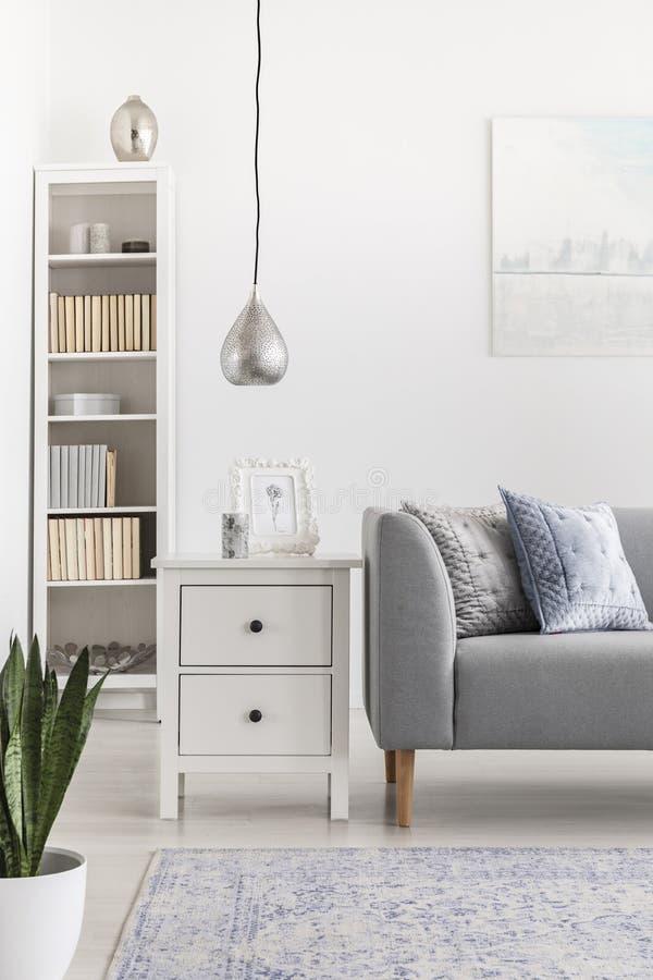 Försilvra lampan ovanför kabinettet bredvid den gråa soffan i vit vardagsrum som är inre med bokhyllan Verkligt foto royaltyfri foto