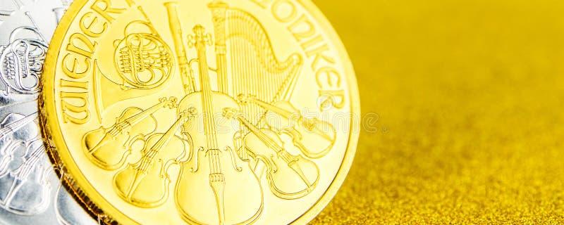 Försilvra och guld- österrikiska phillharmonikers ett uns mynt på guld- bakgrund royaltyfria bilder