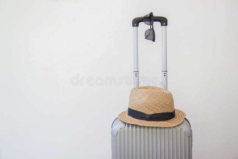 Försilvra resväska- och strandhatten som isoleras på en vit bakgrund arkivfoto