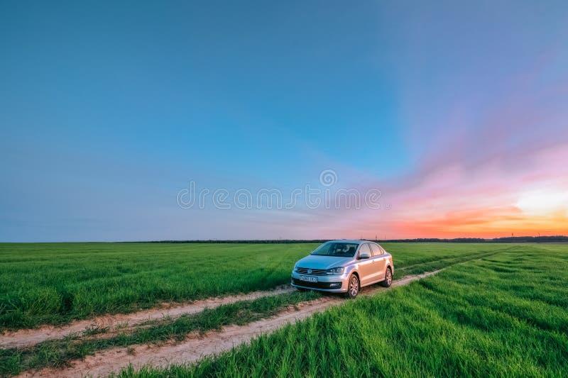 Försilvra sedan Volkswagen Polo Vento i fältet på solnedgången Dobru arkivfoton