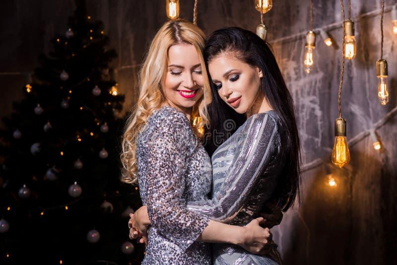 Försilvrar härlig brunett två och blonda kvinnor in sparkly klänningar för julgranen och ljusen Ferier nytt år, royaltyfri fotografi