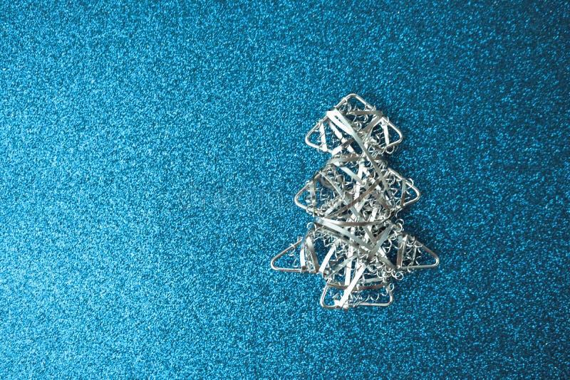 Försilvrar lycklig blå skinande glad bakgrund för festlig jul för det nya året med ett litet leksakmetalljärn den hemlagade julgr arkivbild
