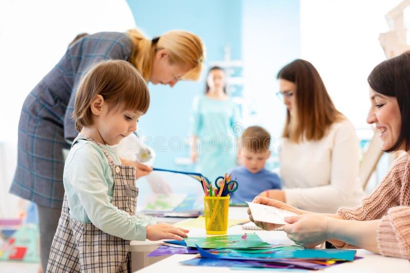 Förskole- barn som arbetar med färgpapper, sciccors och lim på konstgrupp i dagis arkivfoton