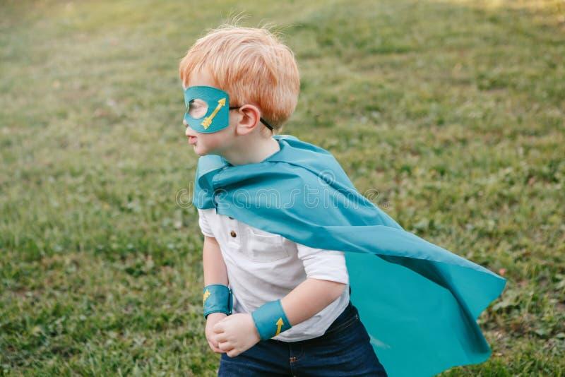 Förskole- Caucasian barnpojke som spelar superheroen i grön dräkt royaltyfri foto