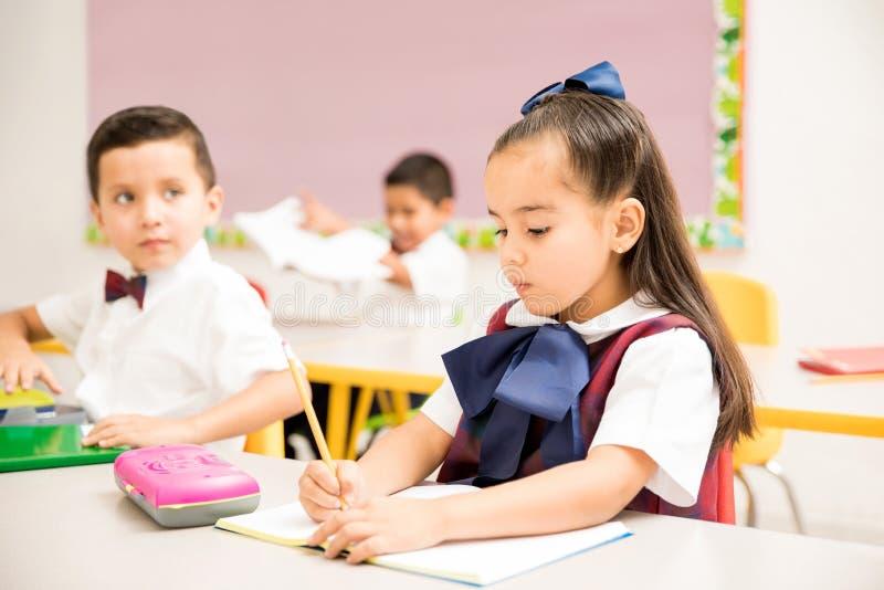Förskole- elever som skriver i ett klassrum royaltyfri bild