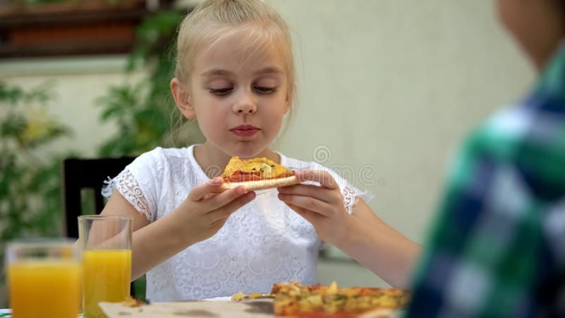Förskole- flicka som äter favorit- italiensk pizza som tycker om smakligt mål, matleverans royaltyfri fotografi