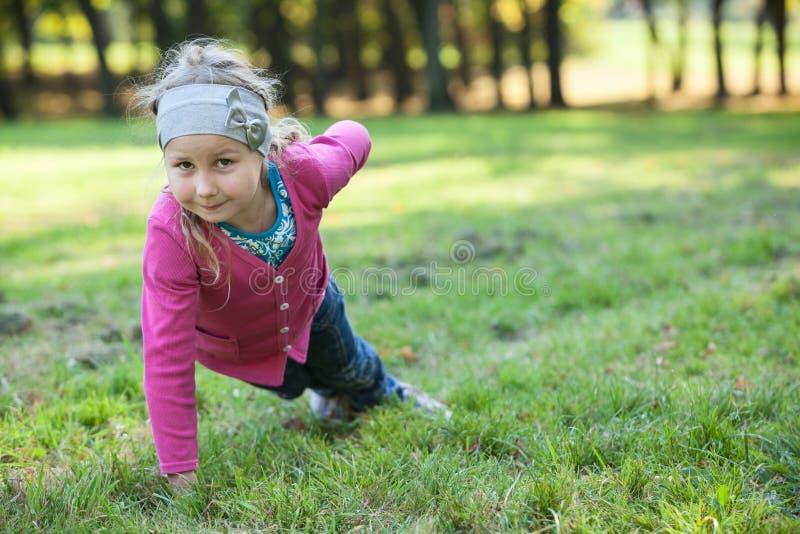 Förskole- flicka som gör push-UPS exercices med en hand på grönt gräs arkivbilder
